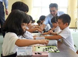 吉岡八段(右奥)からルールを教わり、対局する児童たち=佐賀市の南川副小学校