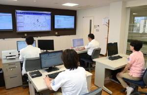 織田病院のMBCの大型モニター(奥)。訪問予定の患者宅などが表示される=鹿島市