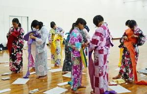 協力して浴衣を身にまとう生徒=有田中体育館