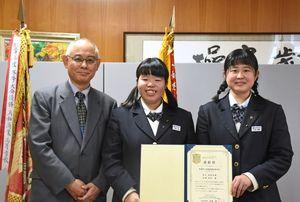 表彰状を手に笑顔を見せる秋吉さん(中央)と谷嶋さん(右)。左は中谷日本政策金融公庫佐賀支店長=鳥栖市の鳥栖商高