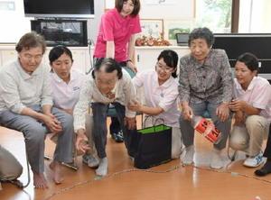 ペットボトルを使ったゲームを楽しむ利用者と神埼清明高の生徒ら=神埼市のもみじの湯