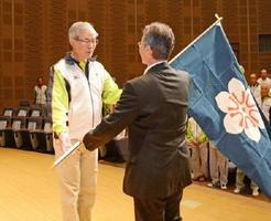 県旗を授与される弓道出場の実本信雄さん(左)