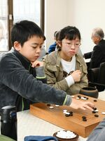 真剣な表情で碁を打つ参加者=佐賀市の日本棋院佐賀中央支部