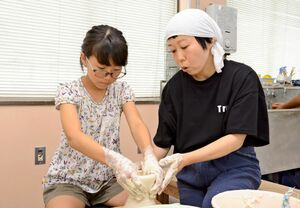 伊万里・有田焼伝統工芸士の白須美紀子さんの指導でろくろの成形に挑戦する児童=有田町のろくろ座