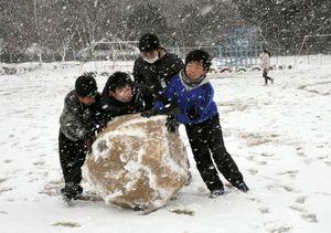 雪の中雪だるまづくりに一生懸命な武雄市の御船が丘小の子どもたち=10日午前9時40分ごろ