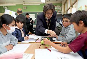 公開授業で、馬場智宏教諭の指導を受けながら、委員会活動を伝えるキャッチフレーズを考える児童=小城市の砥川小