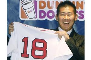 2006年、大リーグのレッドソックスの入団記者会見で、背番号「18」のユニホームを手に、笑顔の松坂=ボストン(共同)
