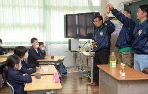 白石産の菜種から生まれた油について子どもたちに説明する「白石菜の花ファーム」のメンバー(右)=白石町の六角小学校