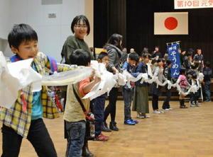 神埼そうめんを1㍍ずつ手に取り、円をつくる来場者たち=神埼市中央公民館