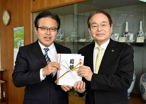 寄付金200万円の目録を手にする黒木祐一郎社長(左)と深浦弘信市長=伊万里市役所