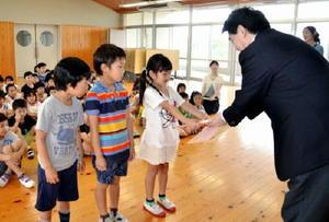 松田基山町長から本を受け取る1年生たち=基山小