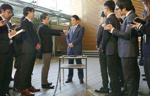 日米首脳電話会談を終え、記者団の取材に応じる安倍首相(中央)=29日午前8時47分、首相官邸