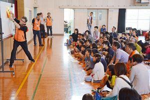 折り紙ヒコーキ滞空時間のギネス記録を持つ戸田拓夫さん(左)から折り方の指導を受ける参加者=佐賀市の開成小体育館