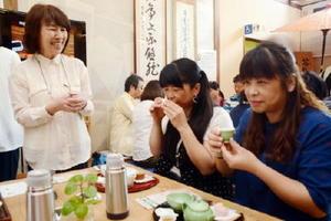 煎茶文化を体験する台湾からのツアー客らと、煎茶の入れ方を教えるNPO法人高遊外売茶翁顕彰会の川本喜美子理事長(左)