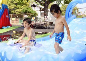 そりに乗って滑り台をすべる子どもたち=佐賀市の神野公園こども遊園地