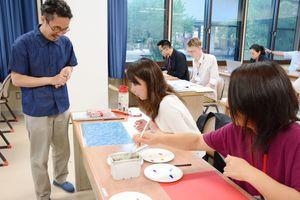 模写に挑戦する受講生に助言する近藤恵介講師(左)=有田町の佐賀大学有田キャンパス