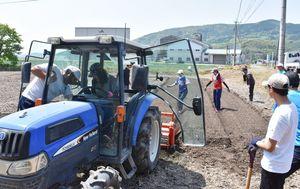 トラクターで畑を整備する学生ら=白石町