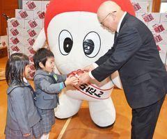 奥崎組合長からリンゴを受け取る園児=佐賀市の佐賀市中央児童センター