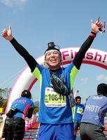 初挑戦のフルマラソンで完走し、両手を挙げて喜ぶ小部亮介記者=県総合運動場補助競技場