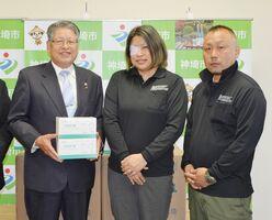 マスク1万枚を贈ったNEXT INNOVATIONの鶴有紀さん(中央)と一心工業の鶴啓介さん(右端)=神埼市役所(市提供)