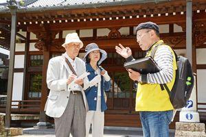 有田の7賢人について観光ガイドから説明を受ける参加者=有田町の報恩寺