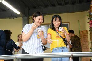 初めてのそうめん流しを楽しむ中国の学生ら=神埼市神埼町の井上製麺