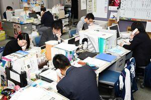 申し込みの問い合わせに対応する事務局の担当者=佐賀市の佐賀新聞社