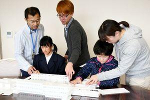 模型を製作した、熊本大の福岡怜大さん(中央)と模型に触れる盲学校の児童生徒=佐賀市の県立盲学校