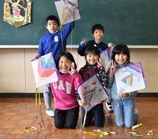 完成した凧をうれしそうに掲げる黒川小の2年生=伊万里市の同校