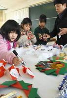 地域の掲示板に付けるクリスマス飾りを作る児童=佐賀市の若楠小学校