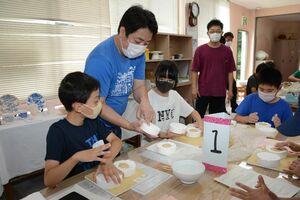 北川朝行さん(左から2番目)の指導で、石こう型に陶土を詰めて箸置きを作る児童たち=有田町泉山の体験工房ろくろ座