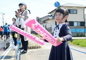 バルーンスティックをたたいてランナーを応援する女の子=神埼市神埼町の給水所
