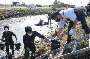 クリークに堆積した泥を取り出す参加者ら=佐賀市本庄町袋