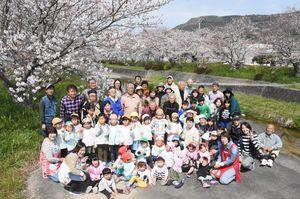 元号「平成」を記念して30年前に植えられた桜の下で半田の皆さん。右奥は鏡山=唐津市半田の半田川沿い