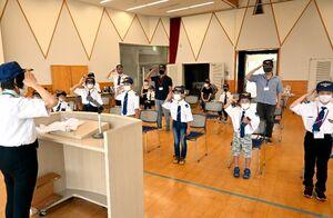 入団式で敬礼をする有明佐賀航空少年団の新入団員たち=佐賀市の春日公民館