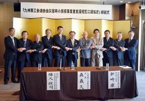 小規模事業者支援の相互応援協定を結び、握手する九州・沖縄8県の商工会連合会代表者ら=福岡市