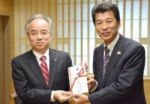 寄付金を贈った前原常務理事(左)と馬場副市長=佐賀市役所