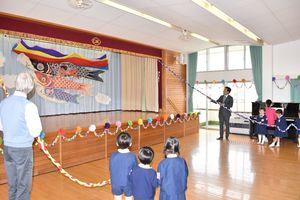 こいのぼりが飾られたステージの幕を開ける山口祥義知事と園児ら=伊万里市二里町の伊万里カトリック幼稚園