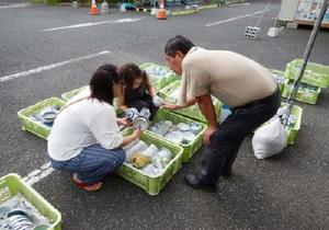 有田焼の茶わんなどを品定めする「ミニ陶器市」の来場者=熊本県益城町の「ユニットハウス村」