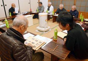 古い写真を見ながら杵島炭鉱閉山50周年記念行事について話し合う有志ら=江北町の新町公民館