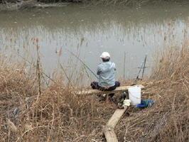 鹿島川で手作りのバンコ(椅子)に腰かけてウナギ釣りをする