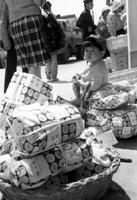 ママは買い物に夢中? ボクは1人で荷物のお守り。記者たちは大人の買い物に付き合わされた、かわいい子どもたちにもカメラを向けた=1970(昭和45)年4月29日、有田町