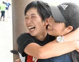 優勝が決まり、後輩と抱き合って喜ぶ竹永萌夏(左)=唐津市の松浦川ボートハウス