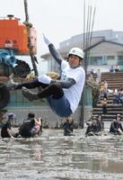 ロープを使い高台から干潟に飛び込むガターザン。飛び方の美しさによる採点と飛距離を競う=鹿島市の七浦海浜スポーツ公園