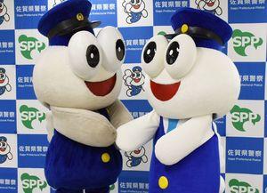 握手を交わす、2代目ごろうくん(左)と3代目ごろうくん(右)=佐賀市の県警本部