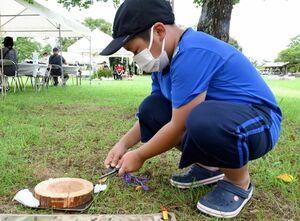 道具を使って、火起こし体験をする子ども=佐賀市の多布施川河畔公園