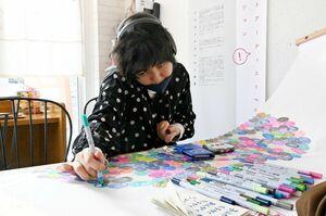 会場で公開制作活動を行う瀬戸口楓子さん。来場者も自由に描き込める=佐賀市のArukカフェ