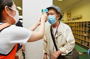 マスク姿で避難所にたどり着き検温を受ける男性=6日午後5時ごろ、佐賀市の神野小