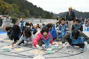 橋の床版(しょうばん)にペンキで自分の顔を描く富士小の児童=佐賀市富士町の古村新橋