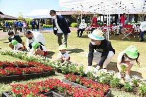 開園20周年記念セレモニーで花壇に花を植える参加者=吉野ケ里歴史公園